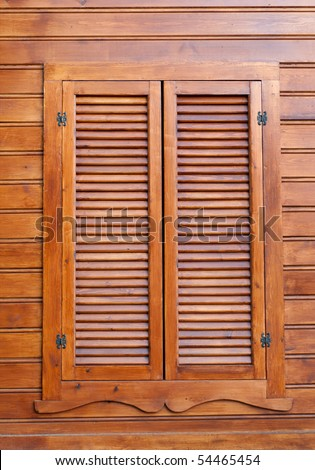 Closed wooden shutters on a wooden panneled wall. - stock photo