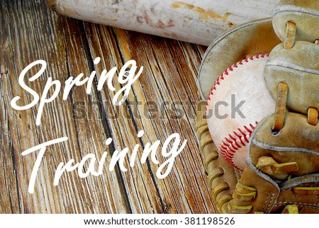 Closely cropped image of old, worn baseball equipment on a wooden background including a bat, mitt and ball. Spring training message added in white cursive text. Horizontal image. - stock photo