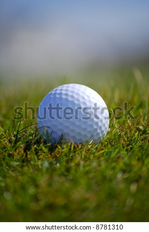 Closely focussed image in a golf ball on grass