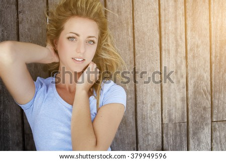 Closely image of a young Sweden model with beautiful eyes lying on a wooden floor background with copy space for advertising text message or promotional content, charming blonde woman posing outdoors - stock photo