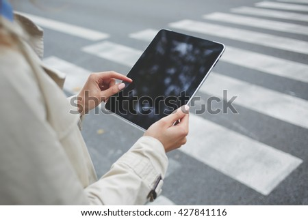 Closely of business person is using banking application via digital tablet, while is waiting on the street car with clients. Close up woman is checking e-mail on touch pad with blank copy space screen - stock photo