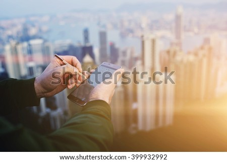 Closely of businessman is writing stylus on touchscreen of mobile phone against blurred New York city. Closeup of male CEO is searching information on web page via cell telephone during work break - stock photo