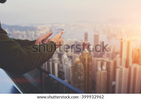Closely of man successful broker is using mobile phone,while is standing on building roof against view of New York city with tall skyscrapers. Hipster guy is connecting to internet via cell telephone - stock photo