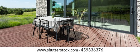 Closer shot of a table and chairs standing at an open area of house terrace in s sunny day, close to the window