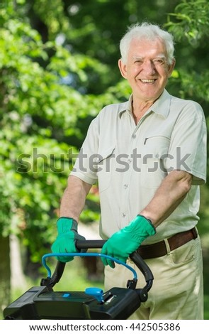 Closer shot of an older man standing with the lawnmower with gloves in his garden and smiling