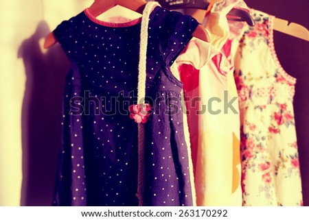 Closet with colorful baby dresses on hangers. Cotton baby belt on a dress in wardrobe with retro vintage view - stock photo