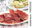 closeup a plate with spanish serrano ham and other tapas - stock photo