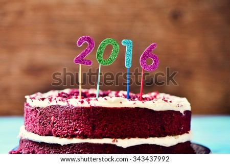 closeup a red velvet cake topped with four glittering numbers of different colors forming the number 2016, as the new year - stock photo