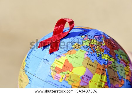 closeup a world globe with a red ribbon for the fight against AIDS - stock photo