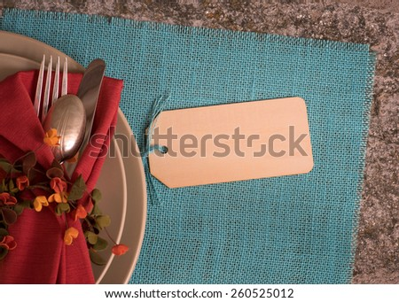 Closeup Above View of a Moody Fall Place Setting with Wood Name Tag on Turquoise Burlap Place mat on Rustic Stone Background with Room or Space for Copy, text, your words.  Horizontal Looking Down - stock photo