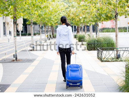Closeup abstract backside view portrait of woman in light blue shirt carrying luggage, walking through gray sidewalk of green trees background.  Path in life is clear but lonely concept - stock photo