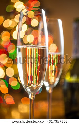 Closeup abstract photo of two glasses with champagne against sparkling Christmas tree - stock photo