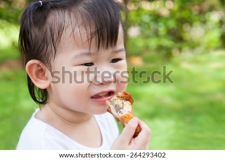 Closeup adorable little asian (thai) girl enjoy eating her lunch in the park, child eating fried chicken over blur green nature background - stock photo
