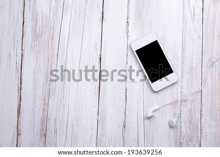 Closeup aerial view of white smart phone with black isolated screen and headphones on white wooden surface. Mockup. Copy space available. - stock photo