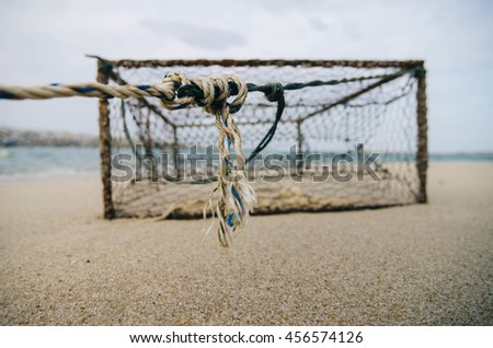 closeup and selective focus on rope over rusty crab pot on the sandy beach.  - stock photo