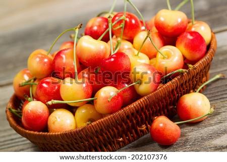 Closeup angled horizontal view of fresh Rainier cherries in basket on rustic wood - stock photo
