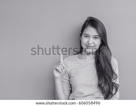 Closeup asian woman holds up one finger with smile face on blurred cement wall textured background in black and white tone with copy space