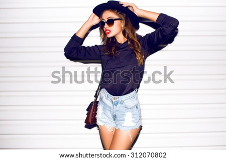 Closeup attractive beautiful woman with fluffy brunette long hairs,smiling, having fun on the white wall,wearing vintage sunglasses,outfit and hat,vacation style,autumn look,hairstyle,hairdresser  - stock photo