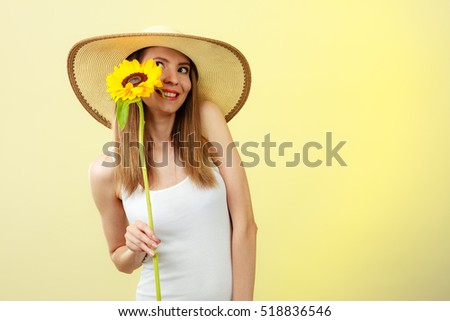 Closeup attractive summer woman in straw hat with sunflower in her hand on yellow background