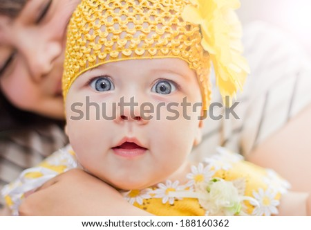 Closeup baby girl in  yeloow with surprised eyes - stock photo