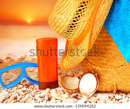 Closeup beach items on sunset on the stony seashore, hygiene accessories, snorkeling mask, sunscreen, hat, bag and towel, summer activities
