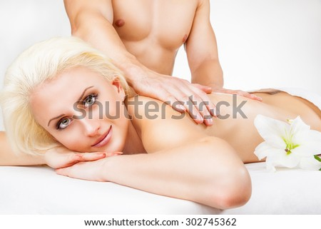Closeup beautiful blond woman getting a massage on a white background  - stock photo