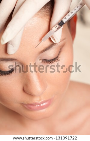closeup beautiful woman face, syringe injection to forehead, beauty concept - stock photo