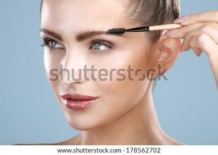 Closeup beautiful woman with eyebrow brush tool on blue - stock photo