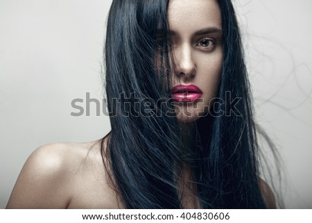 Closeup beauty portrait of a young sensual beautiful brunette sexy woman with long black straight flying hair. Professional nude makeup. - stock photo
