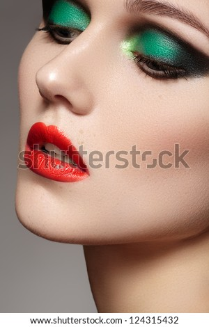 Closeup beauty portrait of attractive model face with bright visage. Chic green eye makeup and red lips make-up - stock photo