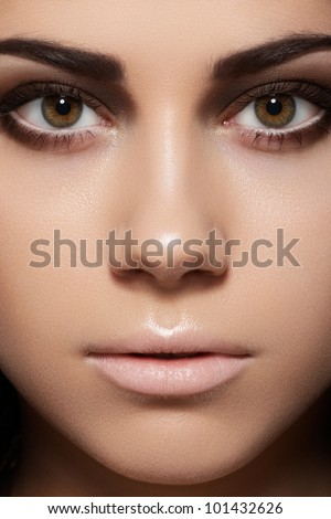 Closeup beauty portrait of attractive model face with fashion visage. Dark brown smoky eyes makeup and beige lips make-up. Evening style