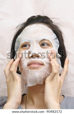 Closeup beauty portrait of beautiful woman with a mask on her face for treatment