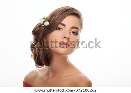 Closeup beauty portrait of young adorable brunette woman with gorgeous makeup low bun hairstyle flower headpiece posing on white studio background - stock photo