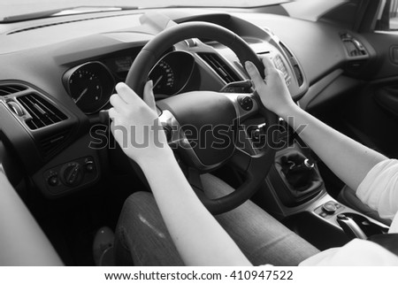 Closeup black and white photo of female hands on car steering wheel - stock photo