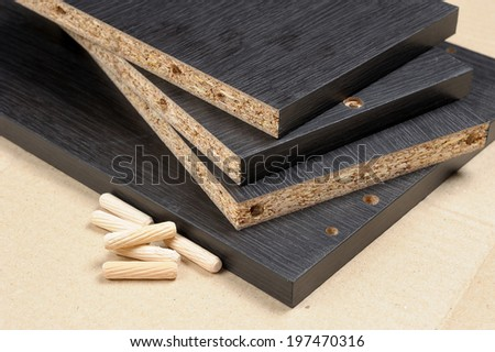 closeup black particleboard and bolt - stock photo