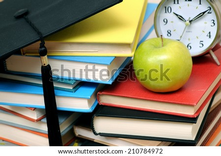 closeup books, graduated cap, clock and apple  - stock photo