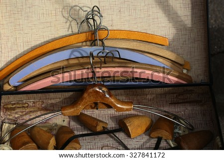 Closeup boot trees and varnish retro wooden coat hanger against lots of vintage clothing hangers angular frames made of timber  painted colored tired aged background, horizontal picture - stock photo