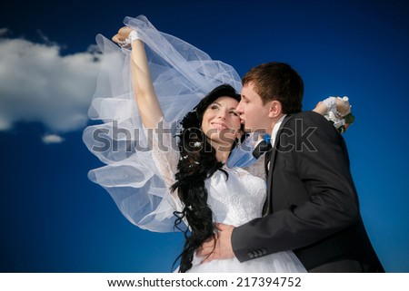 Closeup bride and groom in park on a background of blue sky - stock photo
