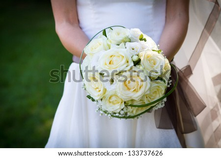 closeup bride holding bouquet of white roses