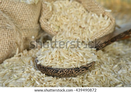 Closeup brown rice on wooden spoon