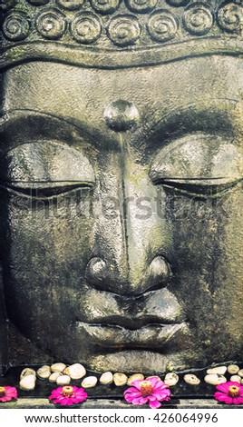 Closeup Buddhist Temple decoration. Buddha face statue with lotus flowers - stock photo