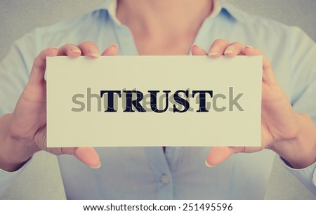 Closeup businesswoman hands holding white card sign with trust text message isolated on grey wall office background. Retro instagram style image - stock photo