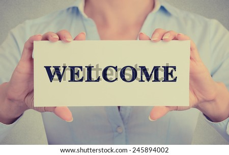 Closeup businesswoman hands holding white card sign with welcome text message isolated on grey wall office background. Retro instagram style image - stock photo