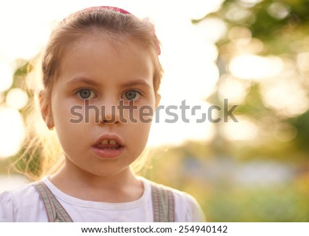 Closeup candid portrait of a little girl gazing innocently at the camera - stock photo