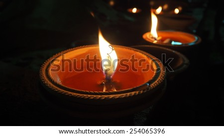 Closeup candles flame in clay pot for meditation at night, black background - stock photo