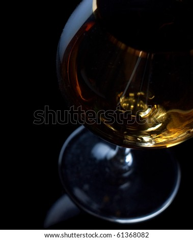 Closeup cognac glass over black background - stock photo