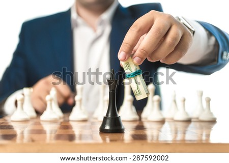 Closeup conceptual shot of businessman in suit make move with dollars in chess game - stock photo