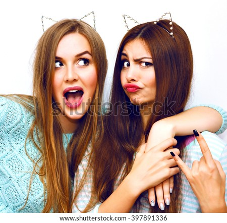 Closeup crazy funny portrait of hipster blonde and brunette sister girls, friendship and emotions, pastel trendy clothes, funny cat ears party accessory, kisses and surprised face, posing on camera. - stock photo