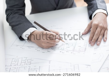 Closeup cropped image of a young male architect working on blueprints spread out on a table - stock photo