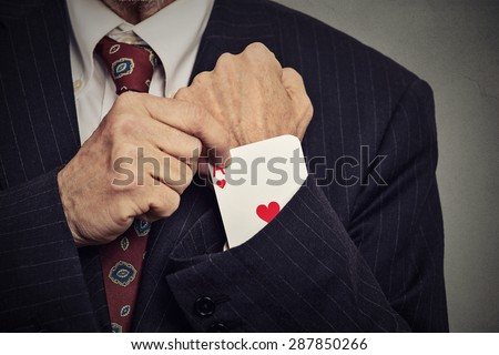 Closeup cropped image senior man hand pulling out a hidden ace from the sleeve isolated on gray wall background  - stock photo